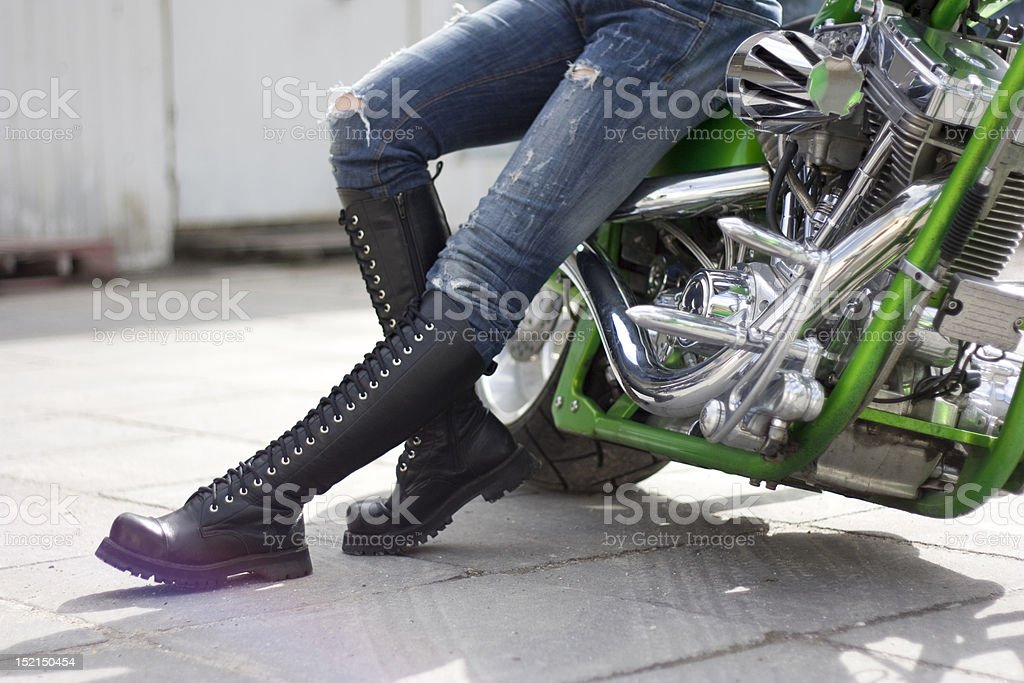 Green motorcycle and a woman in heavy boots near it. stock photo