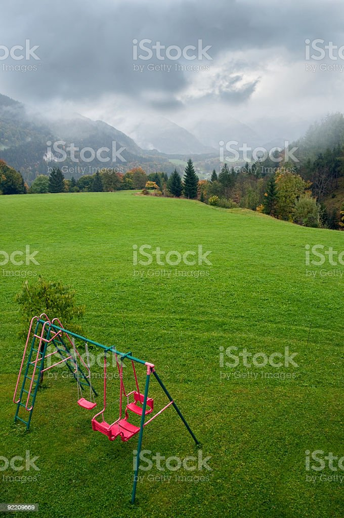 Green mountain pasture dramatic sky playground swing red royalty-free stock photo