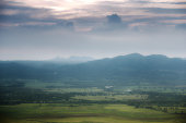 green mountain with fog and cloud sky