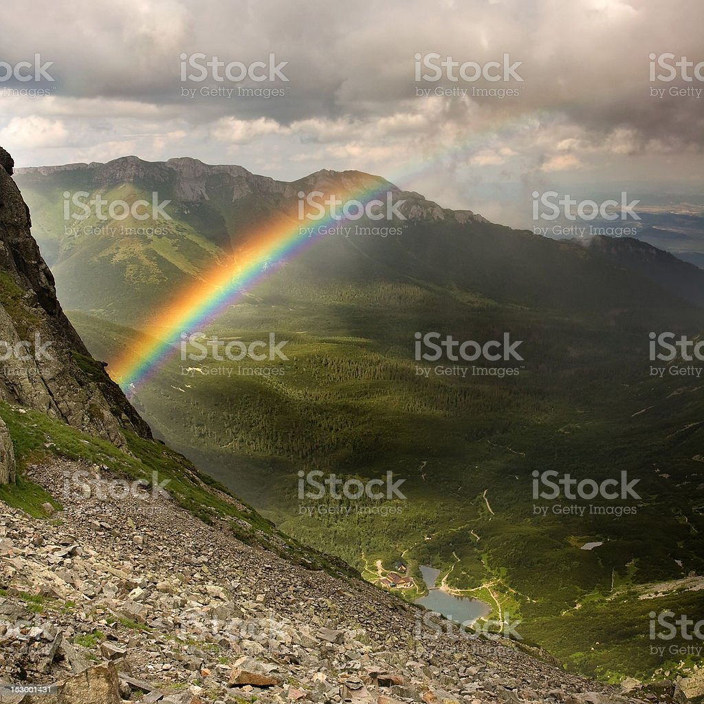 Green mountains, valley, lake, mountain hut and a rainbow stock photo