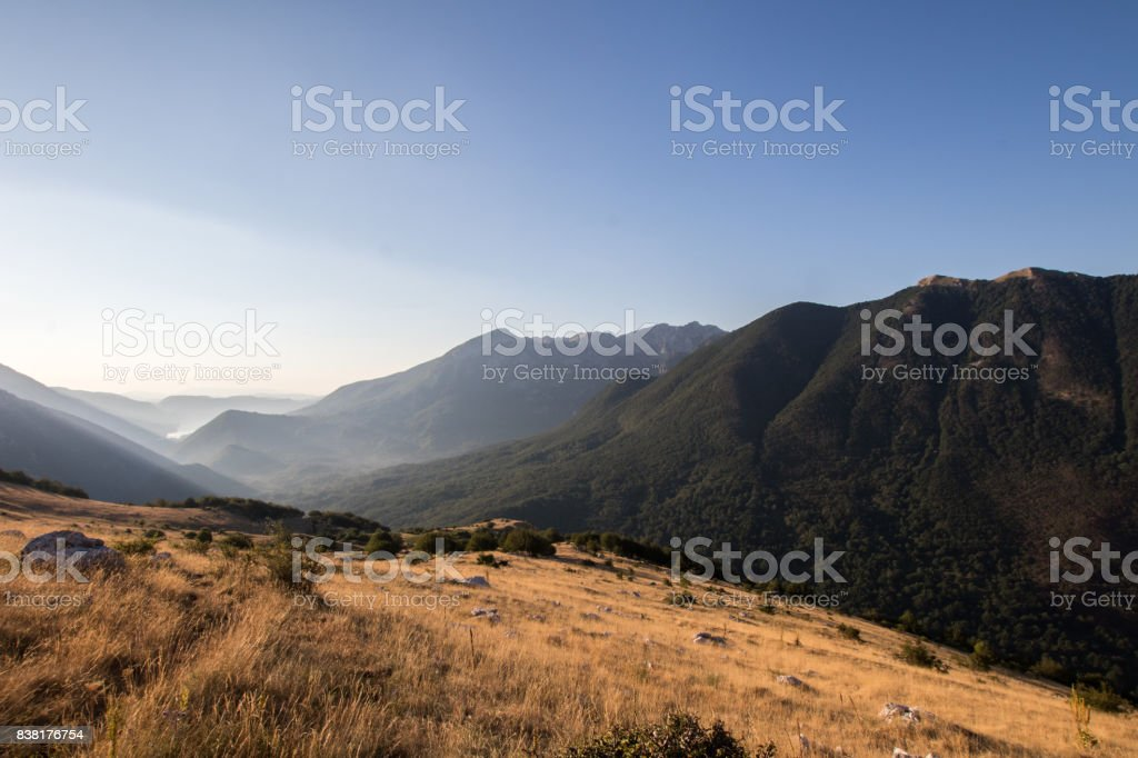 Green mountains with yellow grass fields and lake in the background. stock photo
