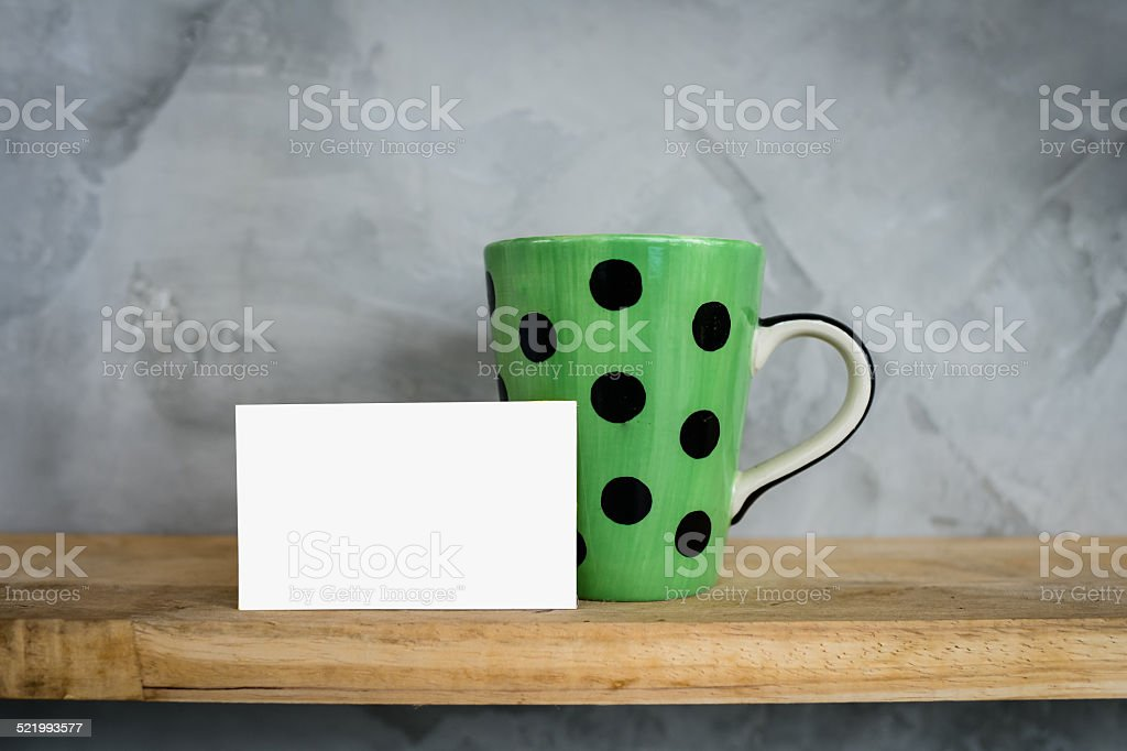 Green mug with dots and blank card on wooden shelf. stock photo