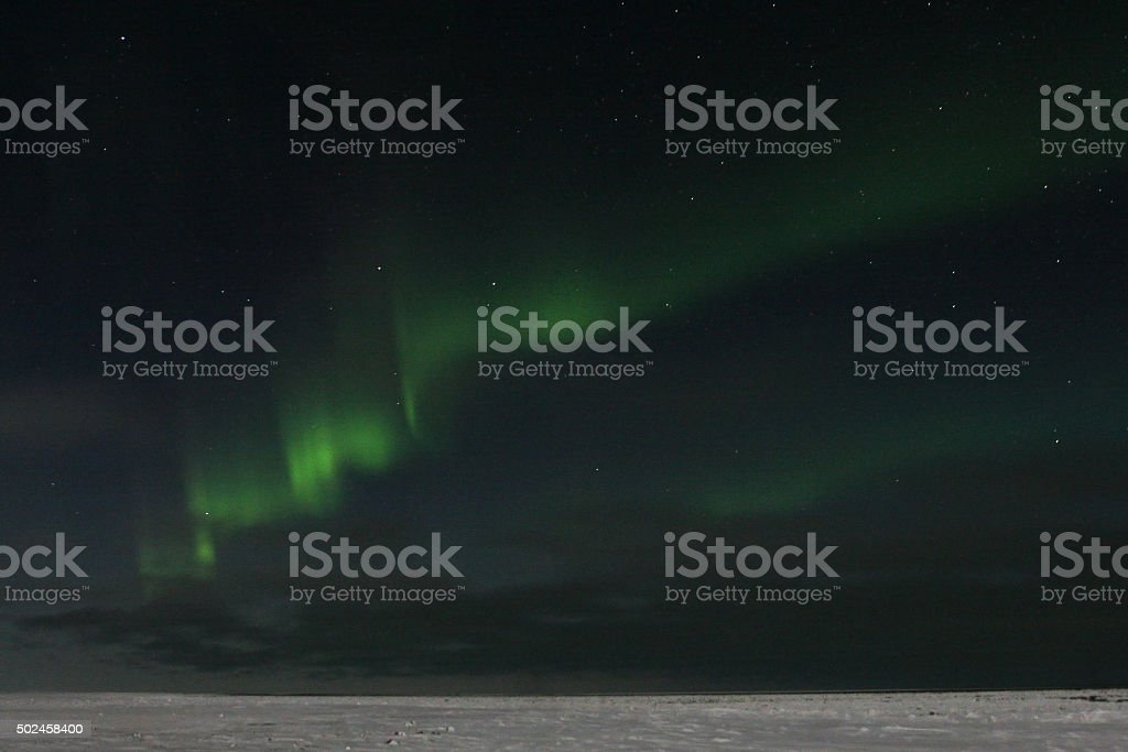 Green northern lights ribbon over snowy arctic Manitoba Canada stock photo