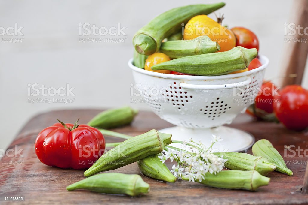 Green okra and tomatoes in white colander. royalty-free stock photo