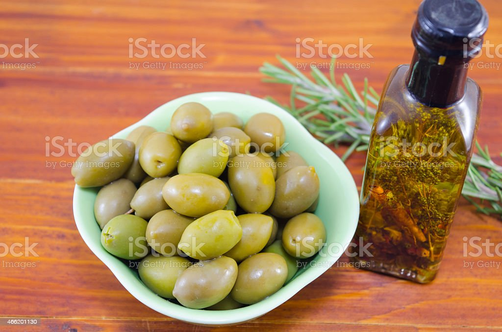 Green olives and a bottle of virgin olive oil royalty-free stock photo