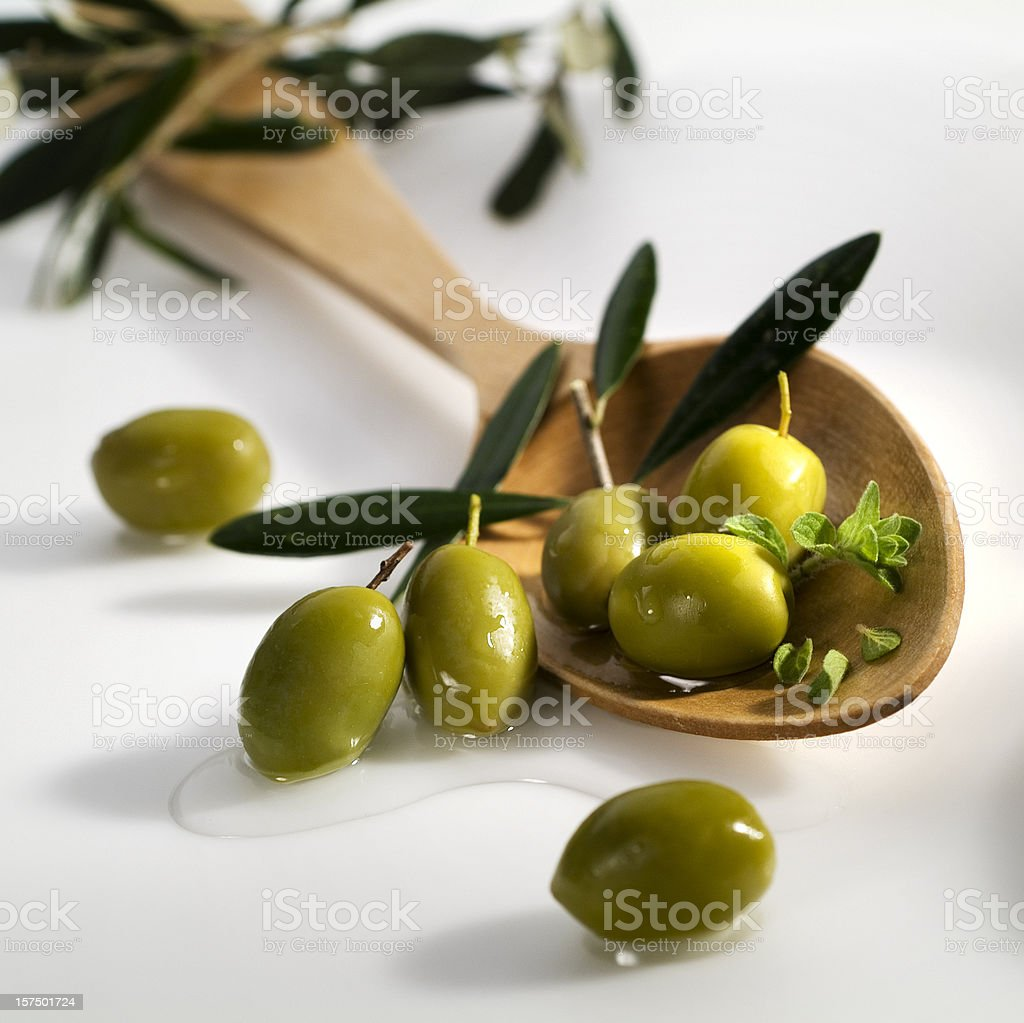 Green olives and a wooden ladle royalty-free stock photo