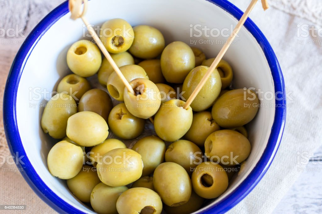 Green olives in bowl on napkin stock photo