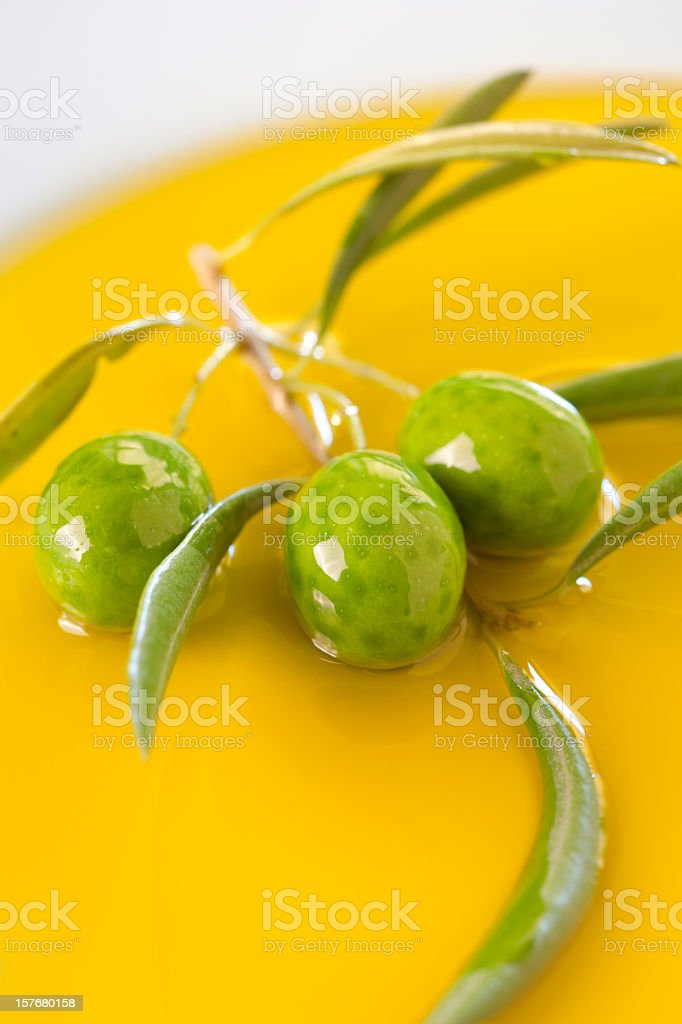 Green Olives in olive oil background stock photo