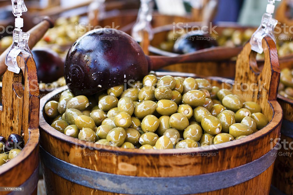 green olives in wooden barrel stock photo