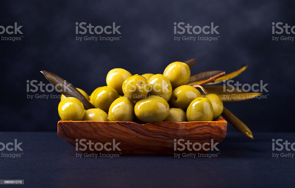 green olives in wooden dish on a black table stock photo
