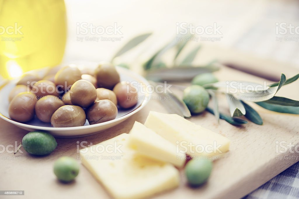Green olives with cheese and olive branch on wooden board stock photo