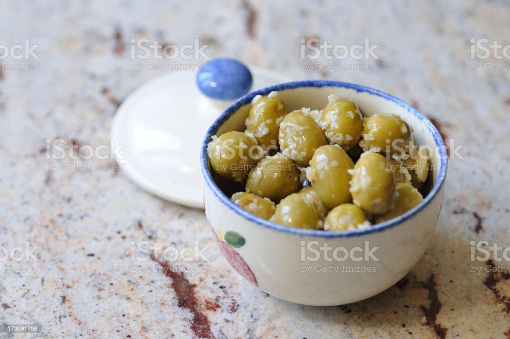 green olives with garlic in bowl stock photo