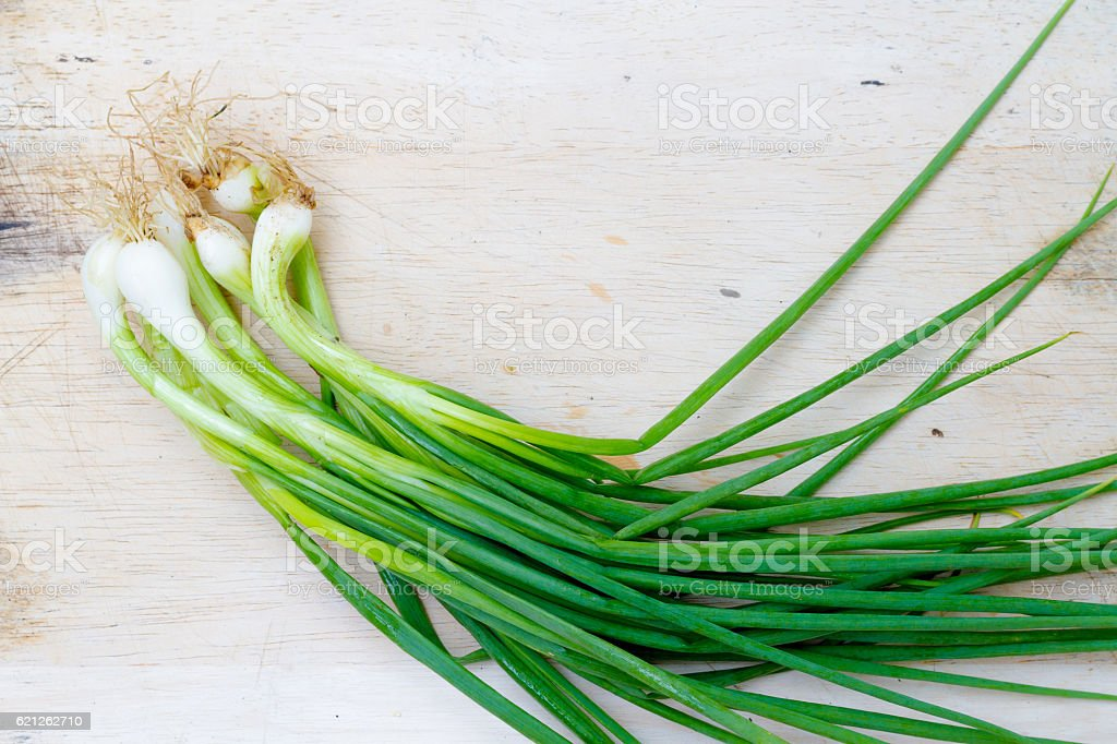 green onions (scallions) in bundle on breadboard table stock photo