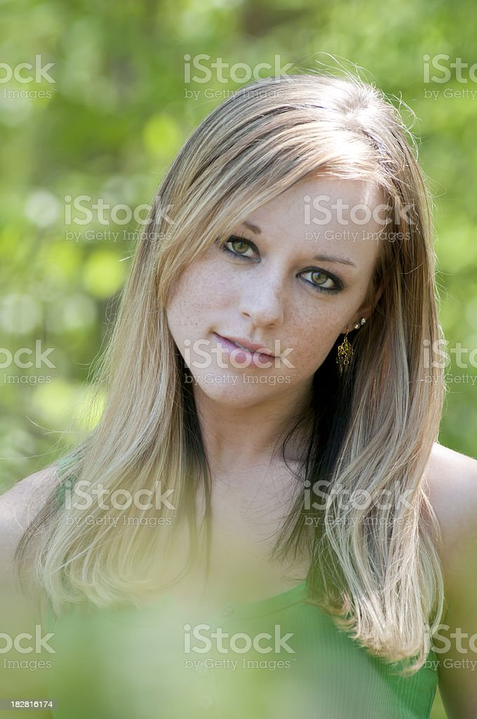 Green outdoor portrait of attractive young woman - III stock photo