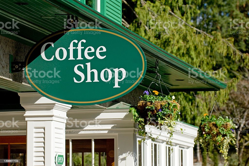 Green oval coffee shop sign hanging on the roof of building royalty-free stock photo