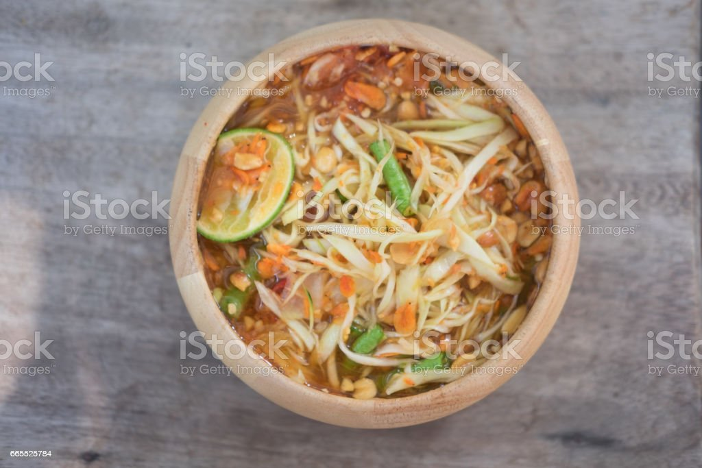 Green Papaya Salad (Som tum Thai) in wooden bowl on wood table Thai cuisine spicy delicious stock photo