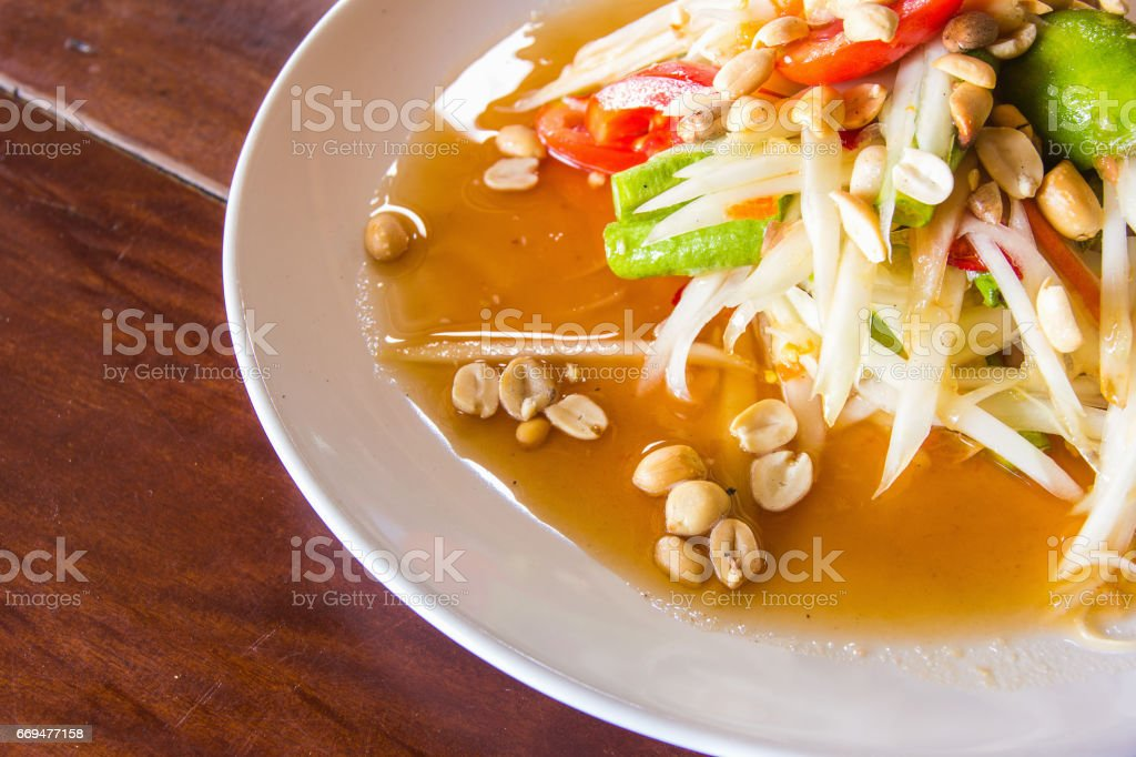 Green Papaya Salad or Som Tum Thai on wooden table stock photo