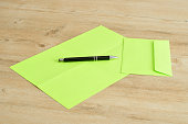 Green paper and envelope with a  pen
