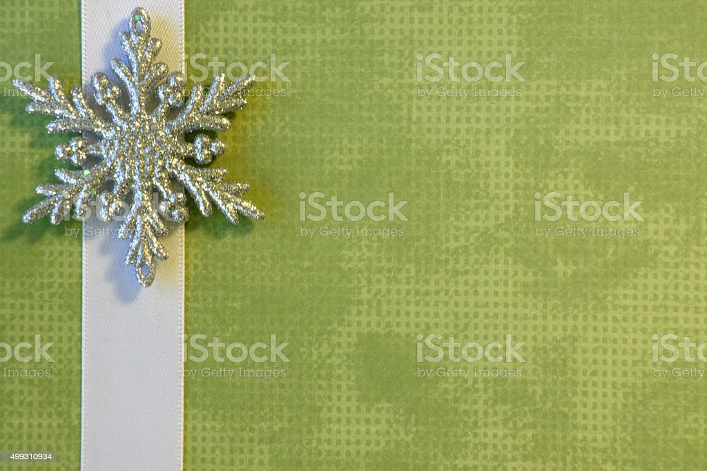 Green Paper Background with a White Ribbon and Snowflake Border stock photo