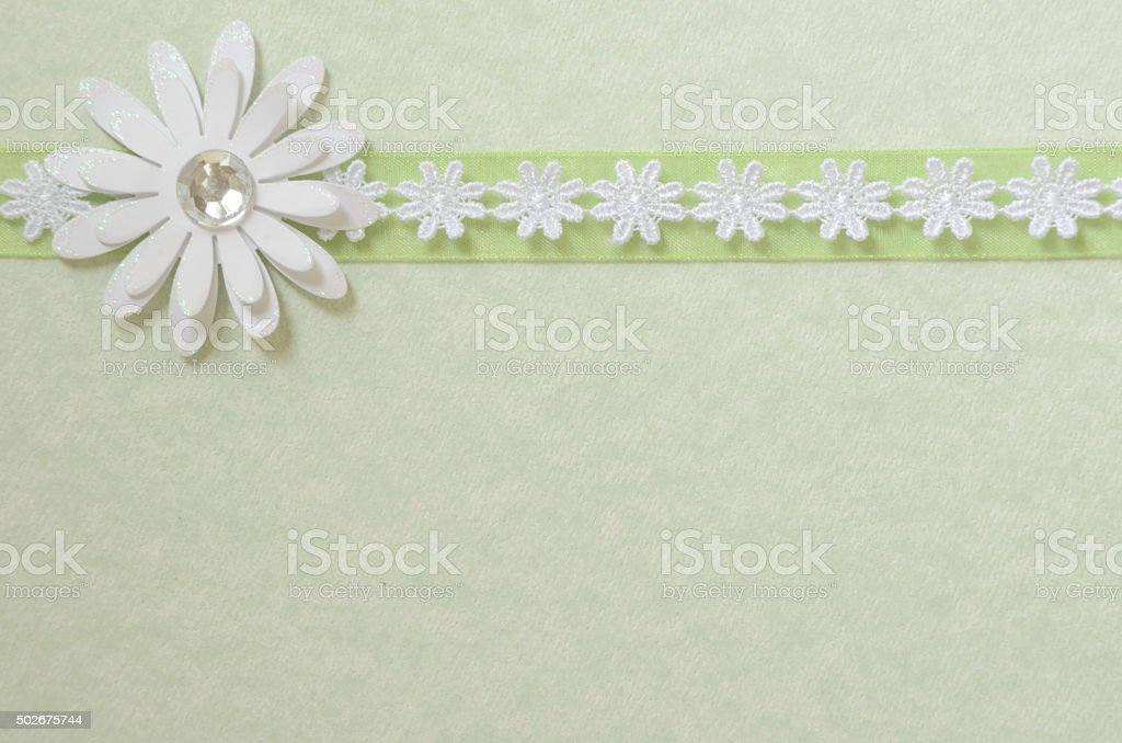 Green Paper with a Ribbon and a Flower stock photo