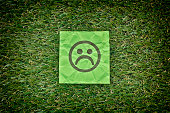 Green paper with sad unhappy face on a green grass