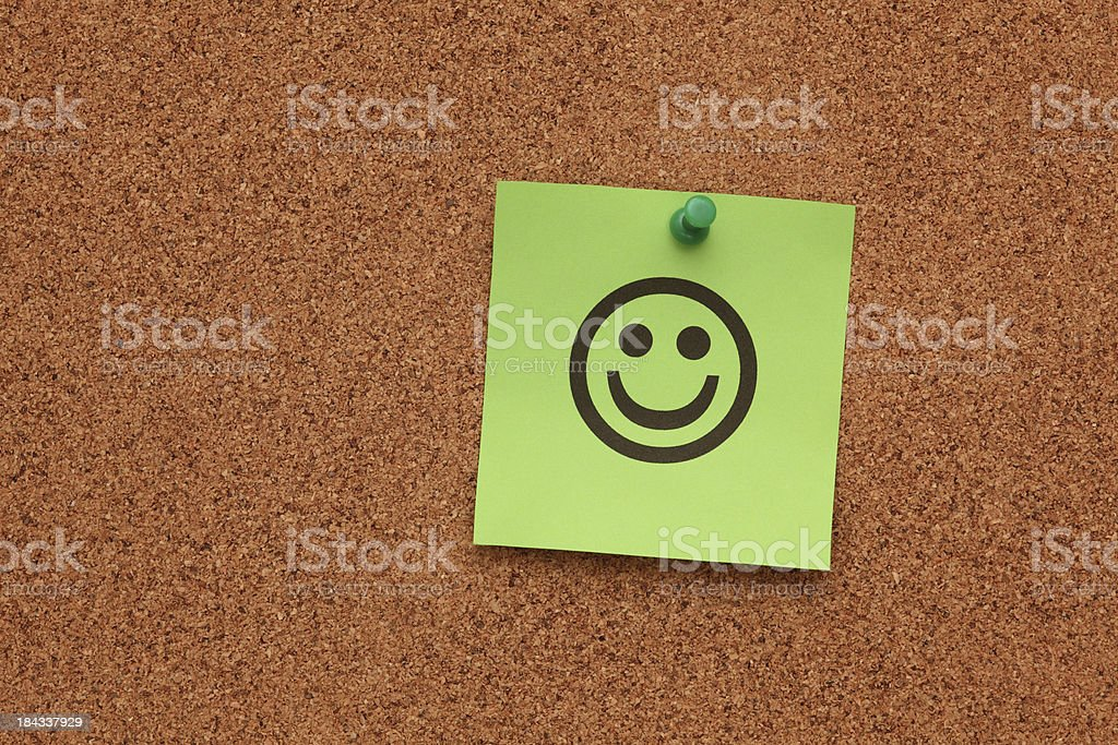Green paper with smiling face on corkboard royalty-free stock photo