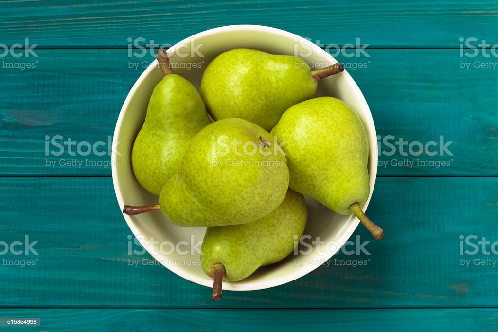 green pears in white bowl on blue wooden background. stock photo