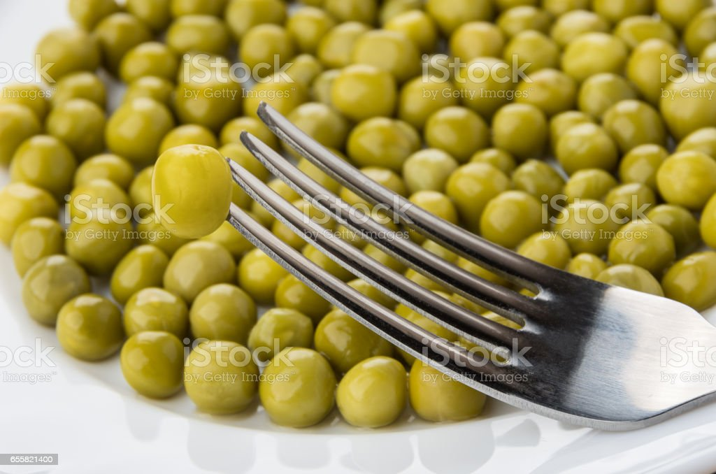 Green peas and fork in plate close up stock photo