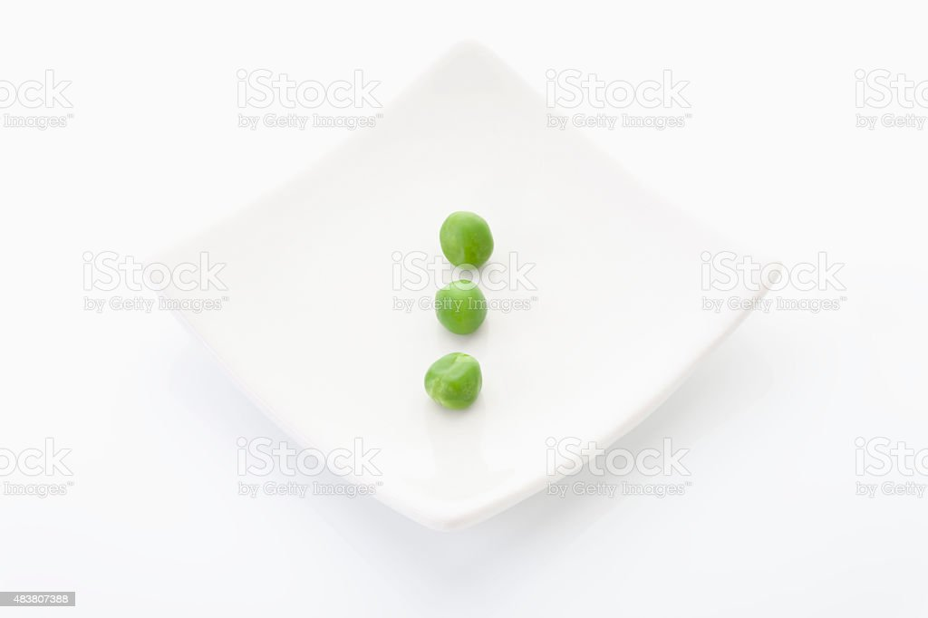 Green peas in plate on white background stock photo
