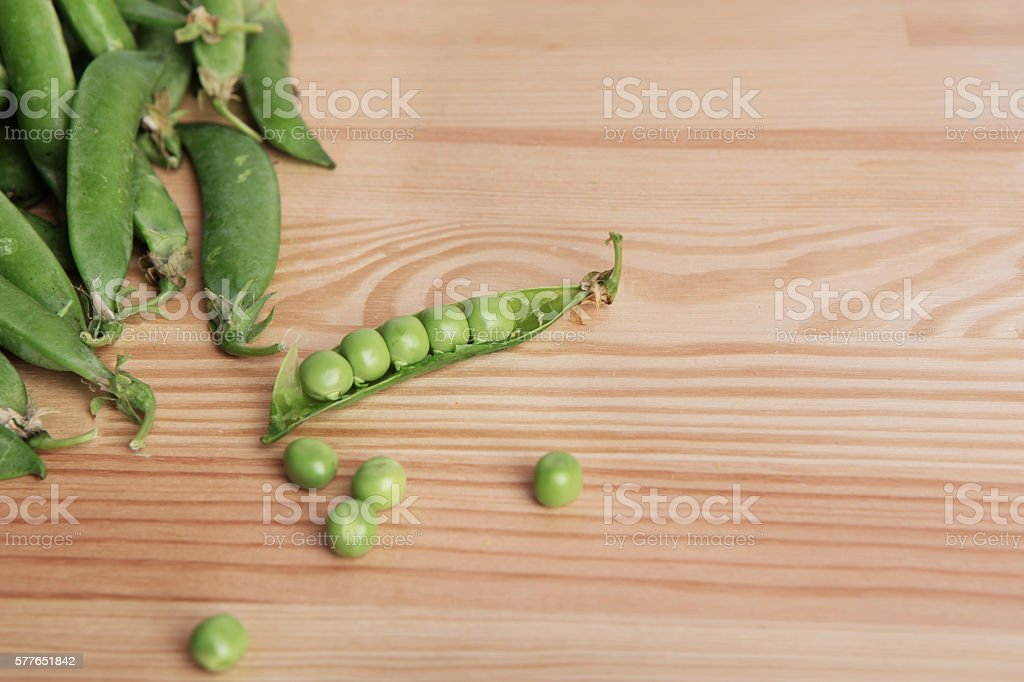 green peas in pods freshly picked on wooden background texture stock photo