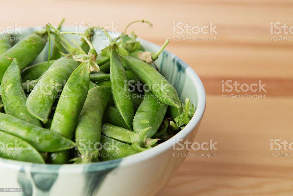 Green peas into a bowl stock photo