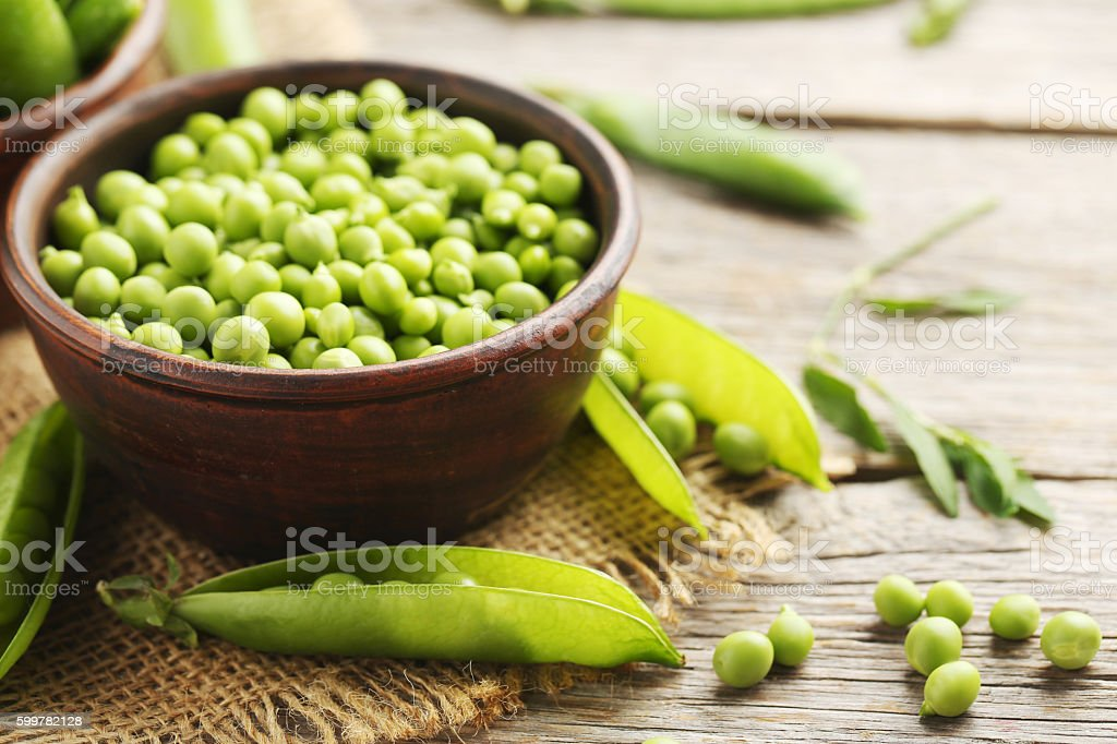 Green peas on a grey wooden table stock photo