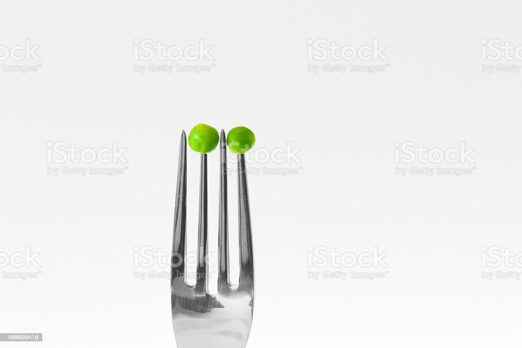 Green peas skewered on fork. Isolated. Diet concept stock photo