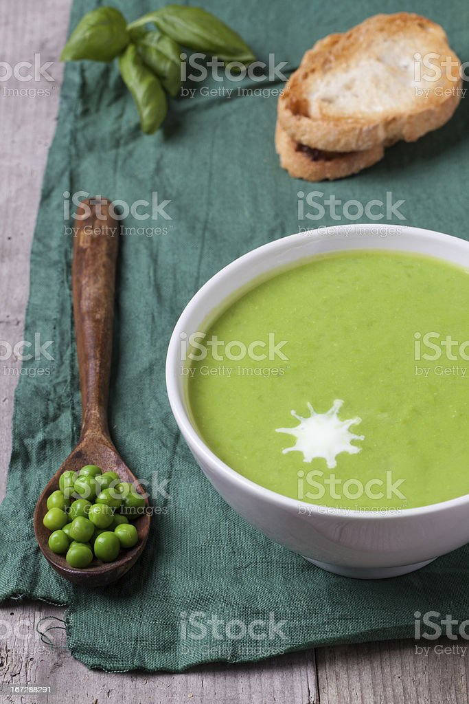 Green peas soup in a white bowl with bread stock photo
