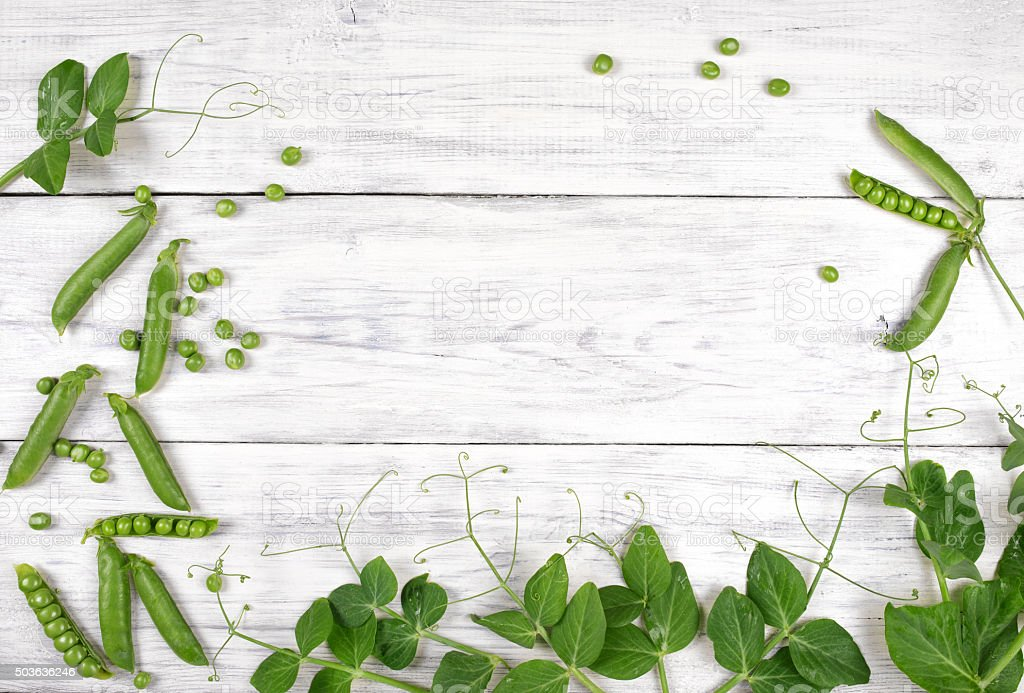 green peas with leaves on white wooden table top view stock photo