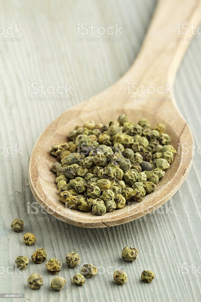 green pepper in a wooden spoon stock photo