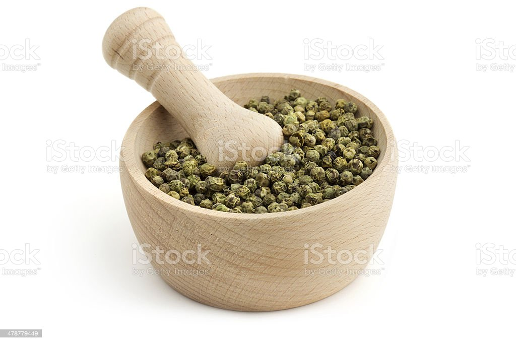 green peppercorns in a mortar stock photo