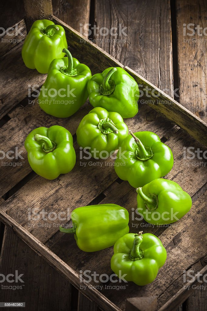 Green peppers group in old wooden box stock photo
