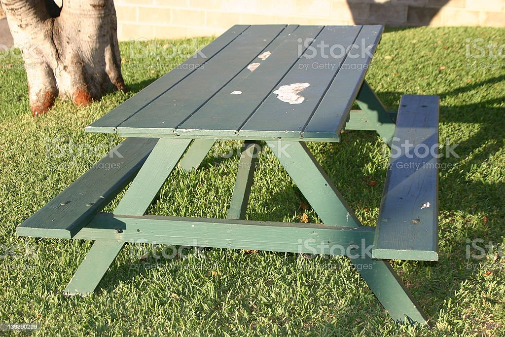 Green picnic table on grass next to a tree royalty-free stock photo