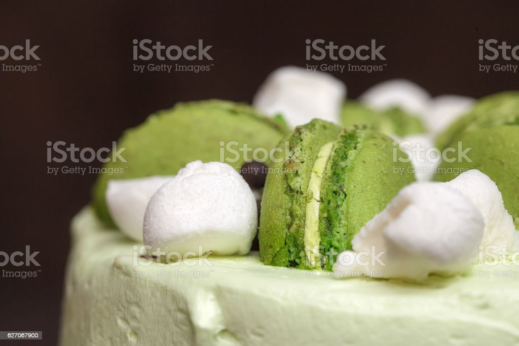 Green pistachio cake with macaroons and marshmallows, closeup stock photo