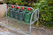 Green plastic watering cans with coin lock on metal shelf