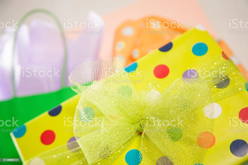 Green, polka dot wrapped birthday gift with party bags. stock photo