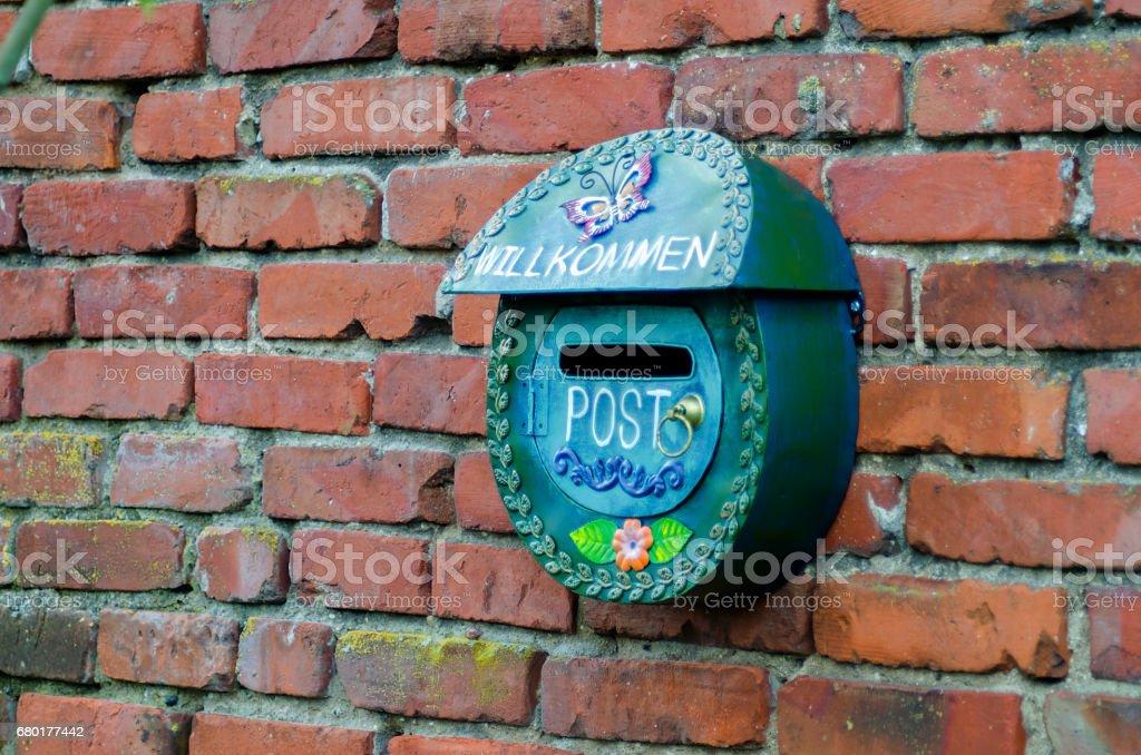 Green Postal Box against red Brick wall stock photo