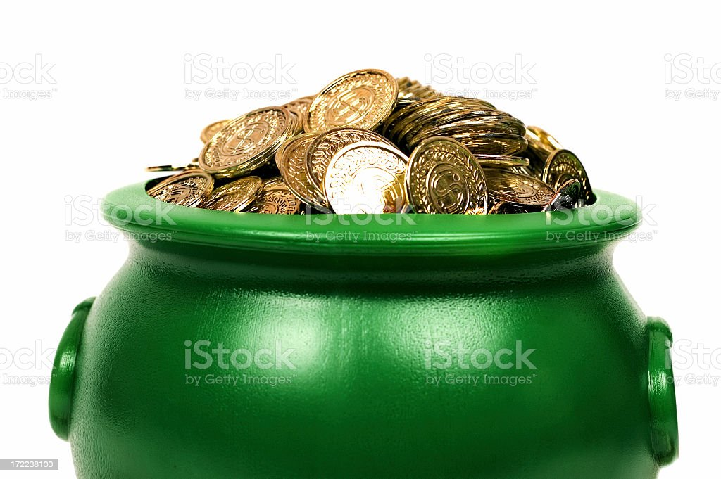 A green pot with lots of gold coins in it stock photo