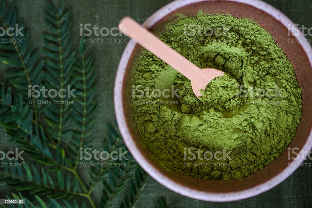 green powder heap isolated on white background stock photo