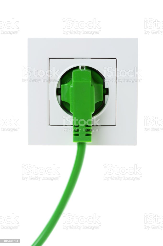 A green power cord plugged into a white wall royalty-free stock photo