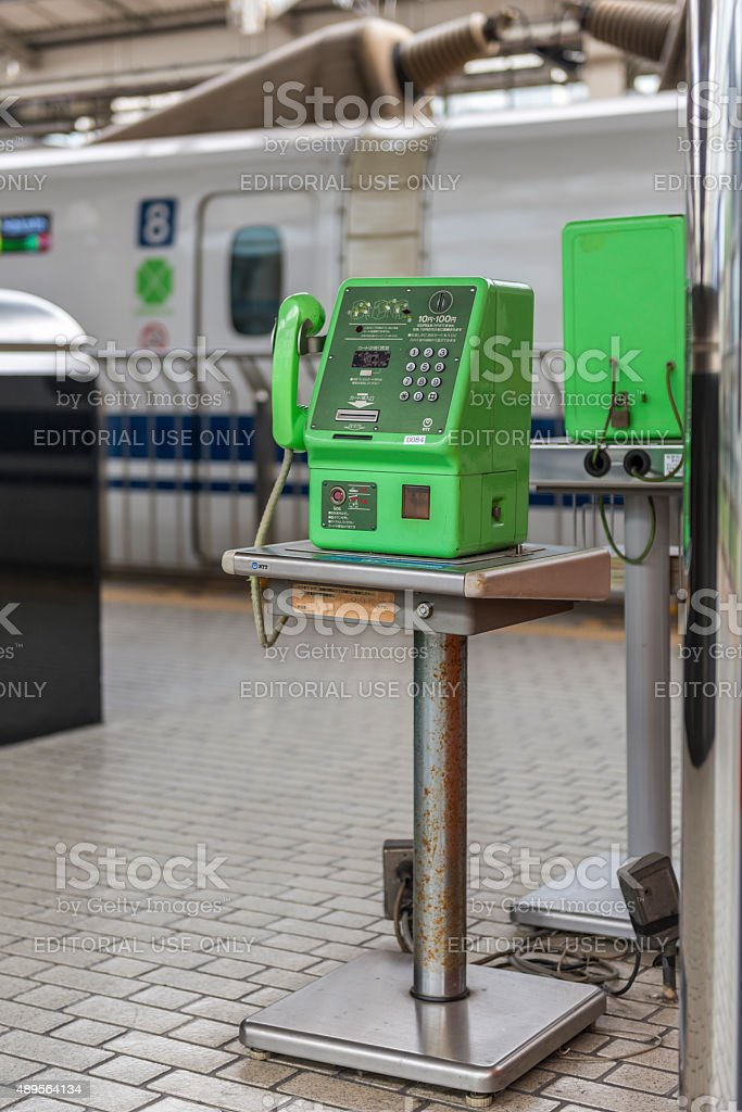 Green public telephone on a station platform stock photo