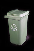 Green recycle rubbish or garbage bin on a black background.