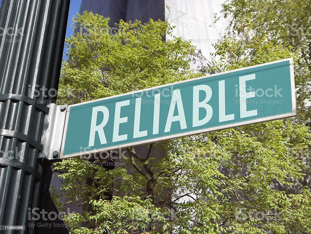 Green reliable street sign with trees behind royalty-free stock photo