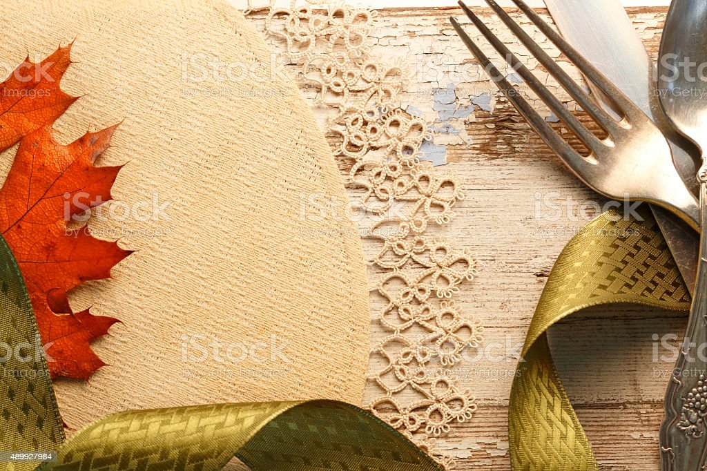 Green Ribbon Wrapped Around Antique Silverware On Old Table stock photo